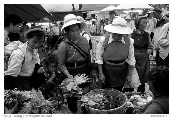 Bai women buying vegetables at the Monday market. Shaping, Yunnan, China
