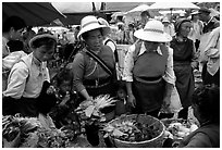 Bai women buying vegetables at the Monday market. Shaping, Yunnan, China (black and white)