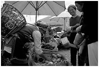 Bai tribeswomen buy vegetables at Monday market. Shaping, Yunnan, China (black and white)
