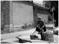 Bai woman fills up a water bucket at the well. Shaping, Yunnan, China (black and white)