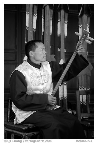 Musician playing a three-stringed traditional moon guitar. Baisha, Yunnan, China (black and white)