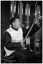 Musician playing a three-stringed traditional moon guitar. Baisha, Yunnan, China ( black and white)