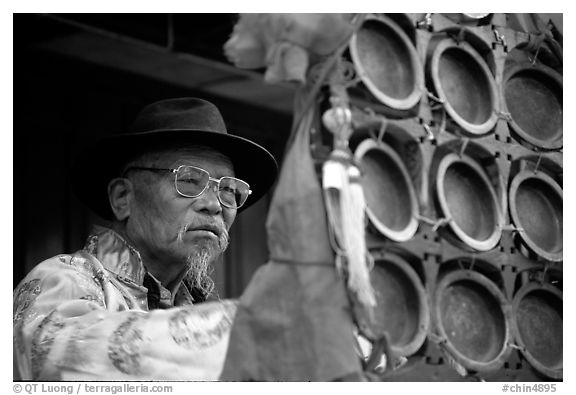 Elderly  musician playing a traditional percussion instrument. Baisha, Yunnan, China (black and white)