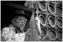 Elderly  musician playing a traditional percussion instrument. Baisha, Yunnan, China ( black and white)