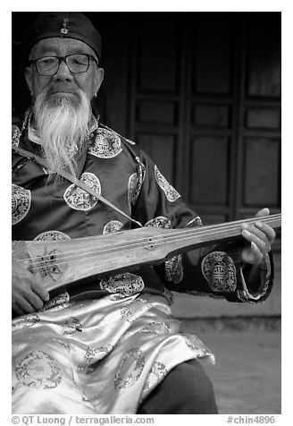 Elderly musician playing the a traditional guitar. Baisha, Yunnan, China (black and white)