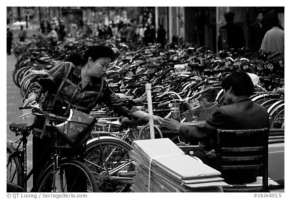 Woman checking out her bicycle at a bicycle lot. Kunming, Yunnan, China (black and white)