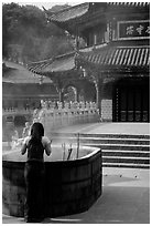 Woman offers incense in the central courtyard of Yantong Si. Kunming, Yunnan, China (black and white)