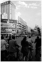 Bicyclists wait for the green light on a modern avenue. Kunming, Yunnan, China (black and white)