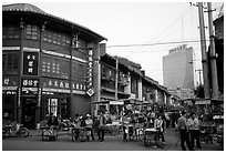 Old wooden buildings, with a high rise in the background. Kunming, Yunnan, China (black and white)