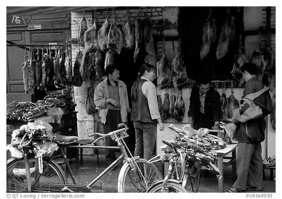 Loading roasted meat on a bicycle. Kunming, Yunnan, China (black and white)