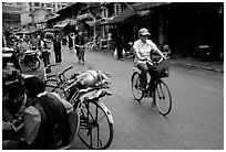 Woman on bicycle in an old backstreet. Kunming, Yunnan, China (black and white)