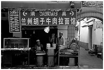 Muslim cooks at restaurant storefront. Kunming, Yunnan, China (black and white)