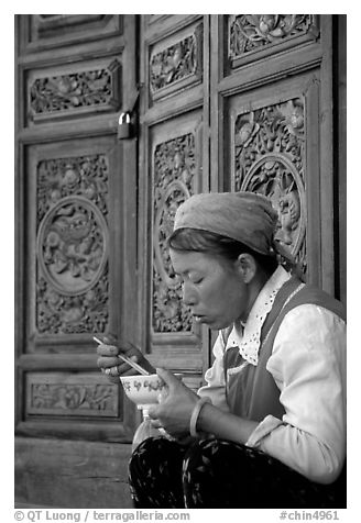 Bai woman eating from a bowl in front of carved wooden doors. Dali, Yunnan, China (black and white)