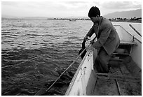 Cormorant fisherman catches one of his birds to retrieve the fish it caught. Dali, Yunnan, China ( black and white)