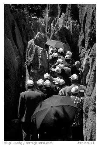 Crowds of Chinese tourists in a walkway among the limestone pillars. Shilin, Yunnan, China (black and white)