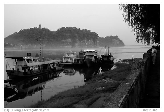 Boats along the river with cliffs in the background. Leshan, Sichuan, China (black and white)