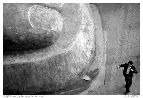 Man standing next to the toe of the Grand Buddha. Leshan, Sichuan, China (black and white)