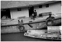 Man sitting on a house boat. Leshan, Sichuan, China (black and white)