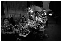 Fruit vendor, night market. Leshan, Sichuan, China (black and white)