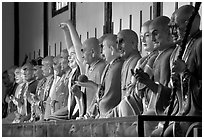 Incredible arrays of postures and expressions of some of the 1000 Terracotta arhat monks in Luohan Hall. Leshan, Sichuan, China (black and white)