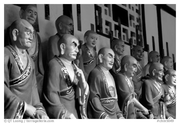 A variety of postures and expressions of some of the 1000 Terracotta arhat monks in Luohan Hall. Leshan, Sichuan, China (black and white)