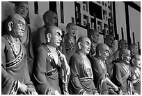 A variety of postures and expressions of some of the 1000 Terracotta arhat monks in Luohan Hall. Leshan, Sichuan, China ( black and white)
