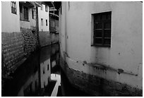 White walled houses surrounding a canal. Lijiang, Yunnan, China (black and white)