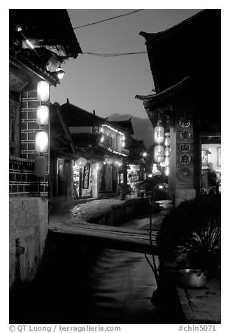 Streets, bridge, wooden houses, red lanterns and canal. Lijiang, Yunnan, China (black and white)