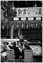 Women eat outside the Snack Food in Lijiang restaurant. Lijiang, Yunnan, China ( black and white)