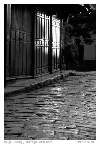 Cobblestone street and wooden doors at sunrise. Lijiang, Yunnan, China (black and white)