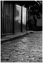 Cobblestone street and wooden doors at sunrise. Lijiang, Yunnan, China ( black and white)