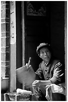 Naxi woman at doorway selling broiled corn. Lijiang, Yunnan, China ( black and white)