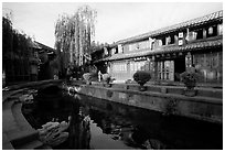 Buildings on Square street reflected in canal, sunrise. Lijiang, Yunnan, China (black and white)
