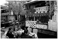 Women eat outside the Snack Food in Lijiang restaurant. Lijiang, Yunnan, China (black and white)