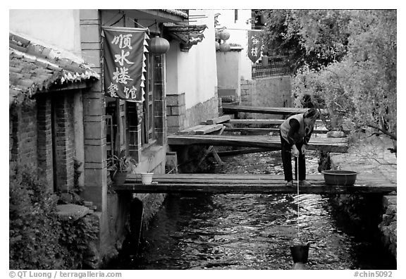Woman fills up a water buck in the canal. Lijiang, Yunnan, China (black and white)
