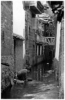 Woman washes clothes in the canal. Lijiang, Yunnan, China (black and white)