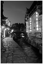 Cobblestone street and canal at night. Lijiang, Yunnan, China (black and white)