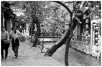 Naxi women walk along a canal. Lijiang, Yunnan, China (black and white)