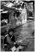Elderly naxi woman peddles candies near a canal. Lijiang, Yunnan, China (black and white)