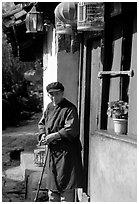 Naxi woman at the door of her wooden house. Lijiang, Yunnan, China ( black and white)