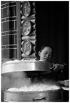 Woman baking dumplings. Lijiang, Yunnan, China (black and white)