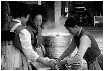 Naxi Women preparing the baba flatbreat. Lijiang, Yunnan, China ( black and white)