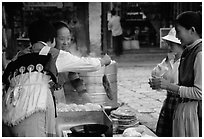 Naxi Women preparing the baba flatbreat. Lijiang, Yunnan, China (black and white)