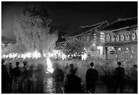 Celebration around a fire in Square Street by night. Lijiang, Yunnan, China (black and white)