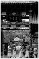 Women in Naxi dress standing in an archway. Lijiang, Yunnan, China ( black and white)