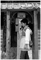 Woman in Naxi dress in a telephone booth. Lijiang, Yunnan, China ( black and white)
