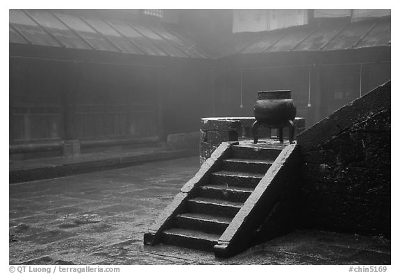 Urn and stairs in courtyard of Xiangfeng temple in fog. Emei Shan, Sichuan, China (black and white)