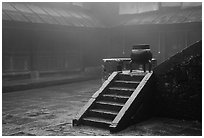 Urn and stairs in courtyard of Xiangfeng temple in fog. Emei Shan, Sichuan, China ( black and white)