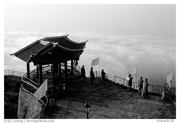 Monks and pilgrims admiring a sea of cloud from the summit. Emei Shan, Sichuan, China (black and white)