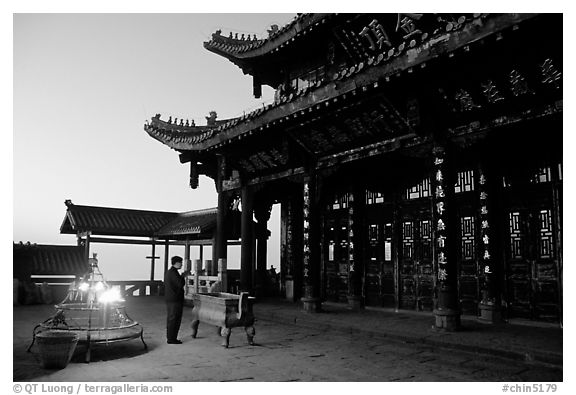 Pilgrim prays in the Jinding Si (Golden Summit) temple at dusk. Emei Shan, Sichuan, China (black and white)